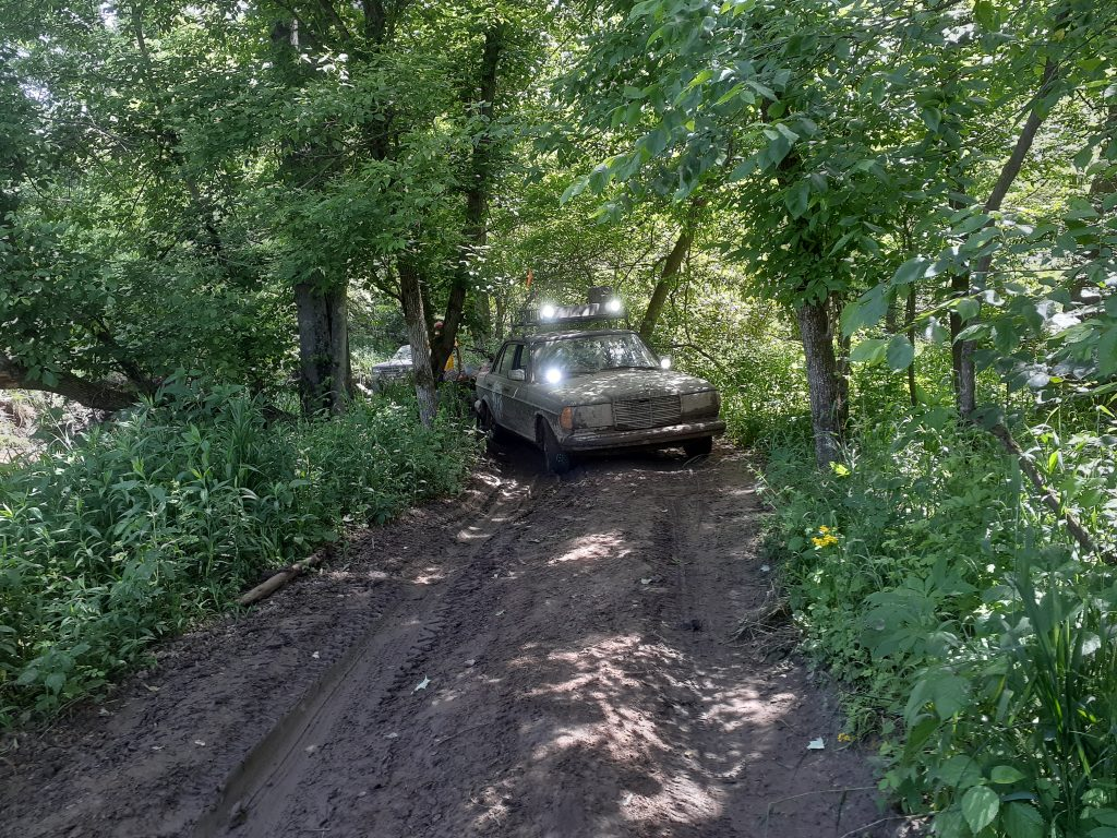 The Mercedes works through a muddy forest.